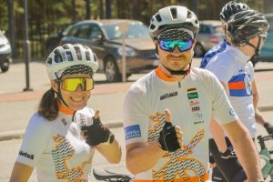 Two happy people with cyckling helmets and glasses on giving thumbs up.